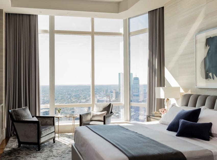 This upscale master bedroom features full-glazed walls framing the city skyline. A pair of plush velvet armchairs with gilded side tables on a matching velvet rug enrichens the space even more.