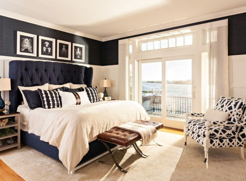 This master bedroom achieves a beach-style effect with the crisp whiteness of the ceiling, wall panelling, and French doors interspersed with layers of moody deep blue from the interior wallpaper and bed with tufted oversize headboard. The chocolate- colored tufted bench at the foot of the bed looks like an island on a backdrop of the cream rug while the white-and-blue armchair unifies the entire look.