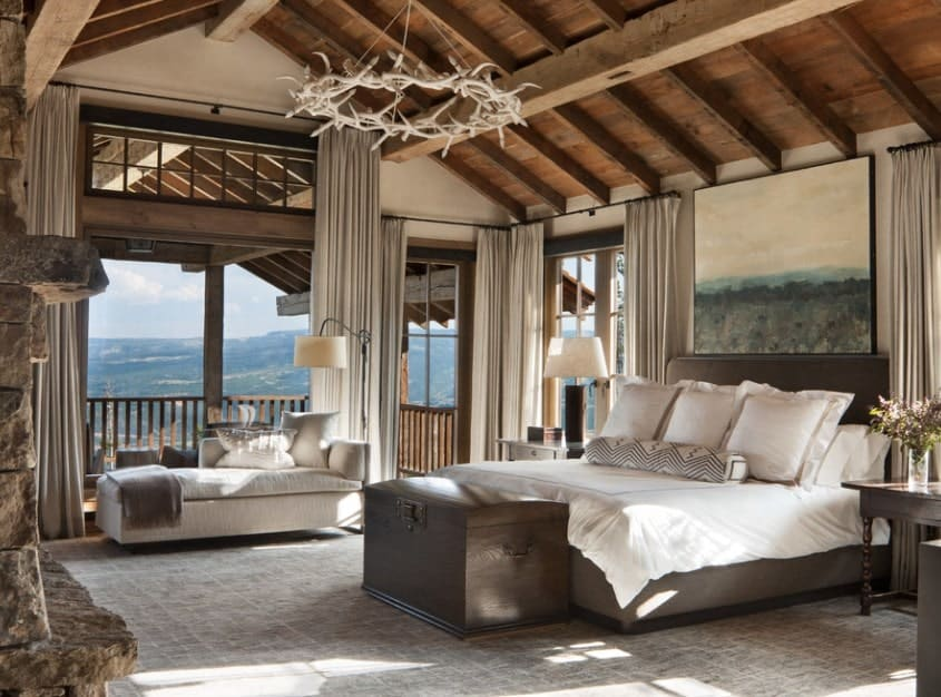 This rustic master bedroom envelopes with warmth and coziness from the pitched beam ceilings to the stone fireplace. The decorative chandelier draws the eyes upward while the floor-to-ceiling draperies conceal the breathtaking views outdoors. A cozy daybed by the window with a floor lamp makes for an ideal lounging spot.