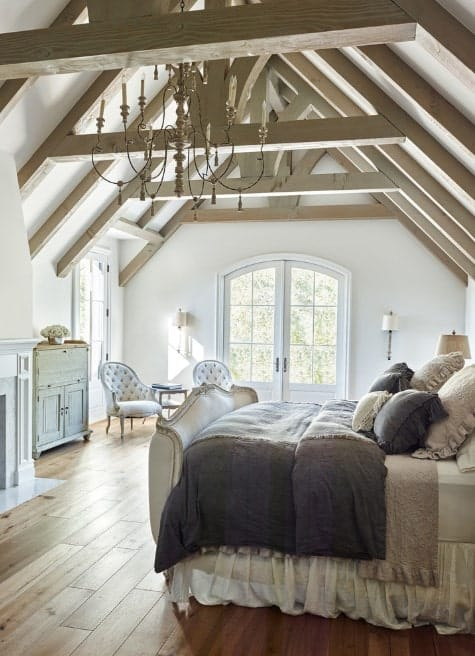 The crisp whiteness of the room heightens the effect of the pitched beam ceiling with the shabby-chic chandelier as well as the dainty touches of the pair of white tufted armchairs near the French doors, the distressed-looking dresser, and bedding of cozy linen.