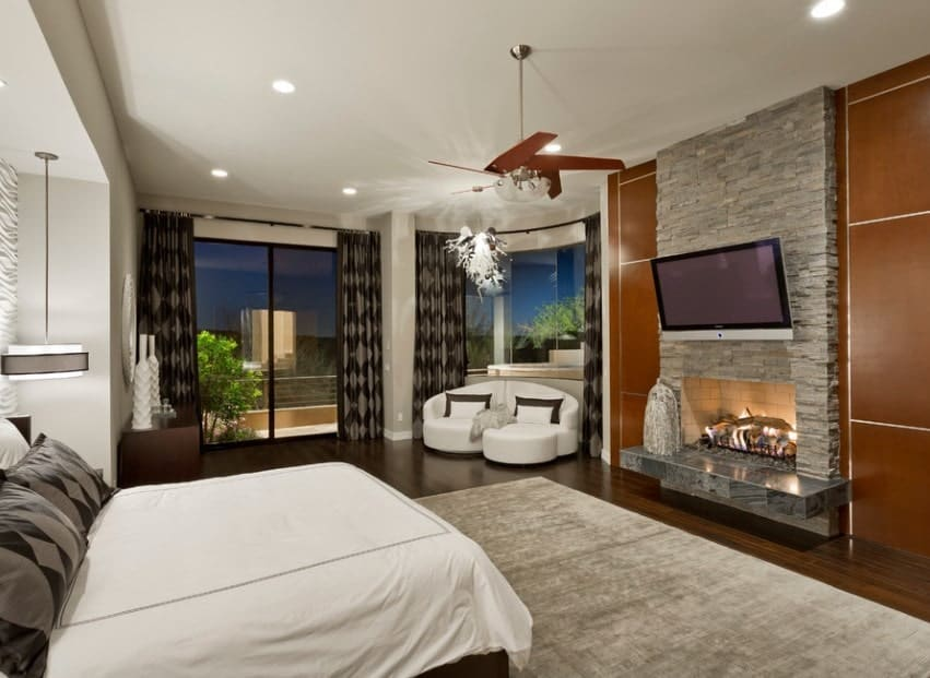 This stately master bedroom is complete with full-glazed walls revealing awesome outdoor views, a white modern sofa that matches the bed, a stone fireplace, a chandelier, and handsome wood flooring.