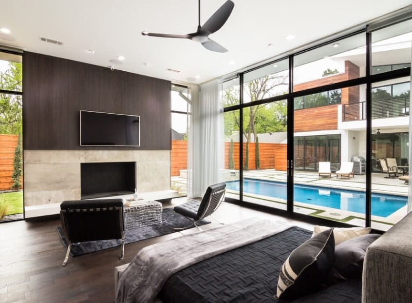 This modern master bedroom features full-glazed walls that almost makes the pretty outdoor a part of it. A black bed and a matching pair of black tufted chairs face the empty fireplace below the wall-mounted TV.