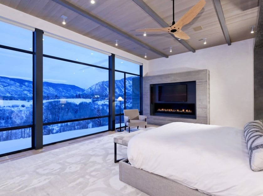 The stunning outdoor views of the ice-capped mountains, trees, and slopes dominate the room with bare white walls, white bed, and a cool gray carpet that makes the room almost part of the outdoors. A lone armchair with a floor lamp by the electric fireplace serves as the best spot for warming up.