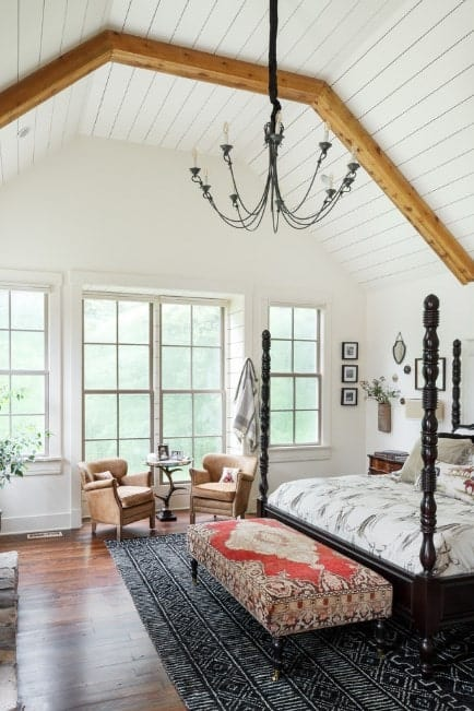 A decorative upholstered bench at the foot of the four-poster bed and standing on the patterned black rug serves as focal points in this classy Farmhouse master bedroom. Beams on the vaulted ceiling and a chandelier create focal points upwards while a pair of armchairs looks cozy in a sweet spot by the bay window.