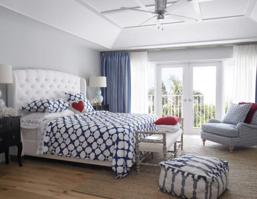 This master bedroom achieves a beach-style look with blue-and-white patterned bedding, ottoman, and armchair as well as the combination of blue and white floor-to-ceiling draperies. The room's visual texture from the tufted oversize headboard, linens, and rug add visual interest.
