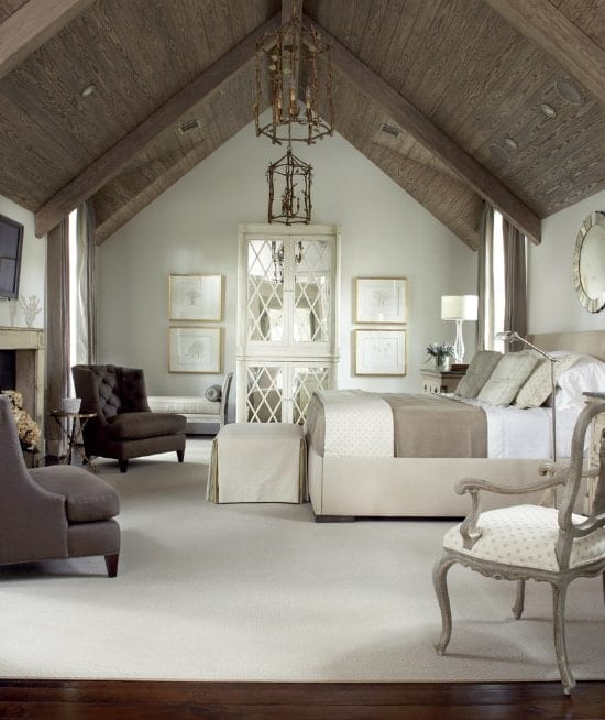 The gray theme in this primary bedroom gives it an elegant look while the patterned linens and visual texture from the tufted wingback chairs and the lattice on the French doors create a dainty look. The pitched beam ceiling with its gilded pair of chandeliers makes the room even more interesting with its rustic addition.