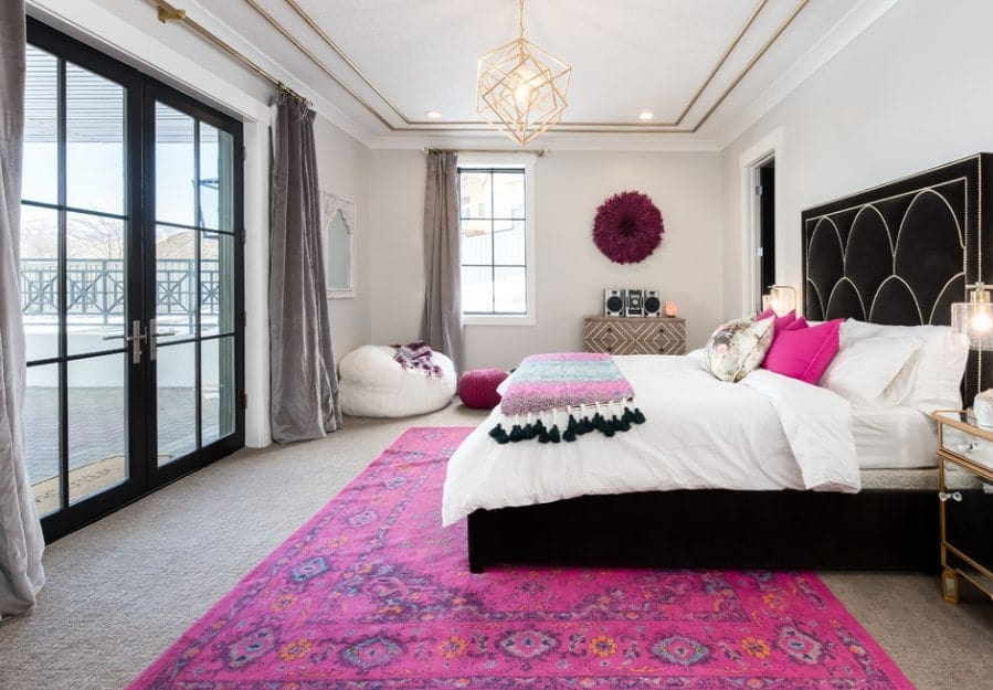 This primary bedroom oozes with a feminine flair from the gilded theme of the tray ceiling and geometric chandelier to the unapologetically pink accessories that sweep over the bed, sitting area, and carpet flooring.