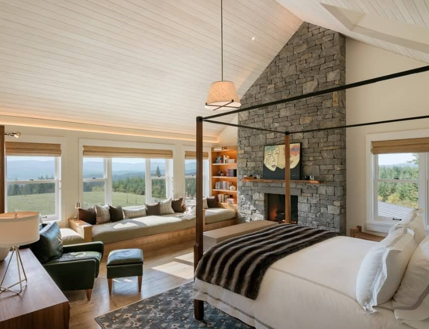 This gorgeous master bedroom offers plenty of focal points from the half stone fireplace that goes way up to the pitched beam ceiling to the built-in window sitting that looks just as inviting as the stunning outdoors behind it.