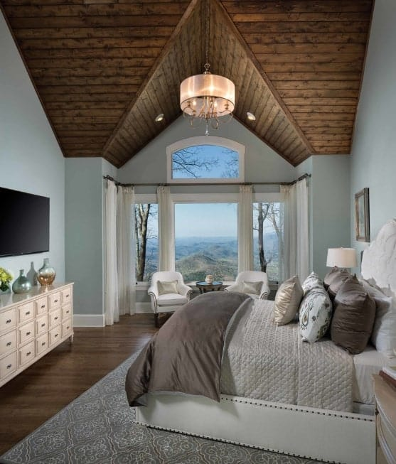 The room's pitched pallet ceiling with chandelier force the eyes upward as it offsets the cool tones of the walls and the beds. A pair of white armchairs by the windows seem to recede into the background as the windows display a fantastic mountaintop view.