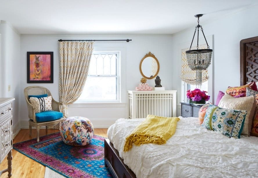 This small eccentric primary bedroom packs a punch of color, personality, and good vibes. The cool tones of the room's ceiling and walls make the room look brighter and refreshing.