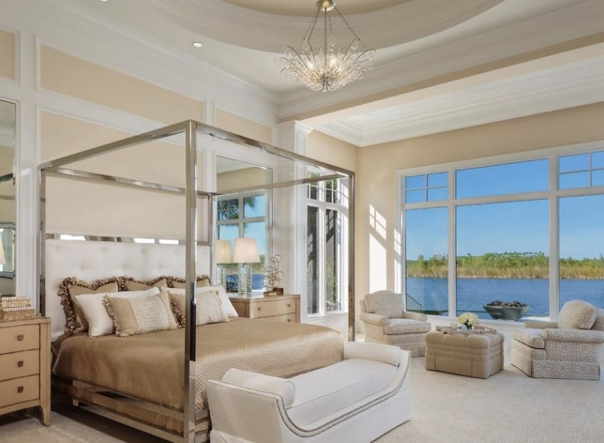 Cream walls broken down with white trims and crown moldings create a classy look for this Traditional master bedroom. The chrome four-poster bed adds a modern touch while a cozy sitting area leads to the inviting outdoor views framed by the windows.
