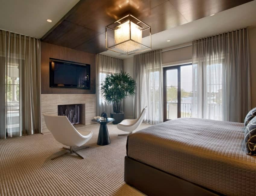 This primary bedroom is wrapped in warm tones from the ceiling to the carpet flooring, creating an intimate and cozy atmosphere. The transparent draperies and the textured look of the bedding and carpet flooring add visual interest while the crisp whiteness of the modern accent chairs stands out in contrast.
