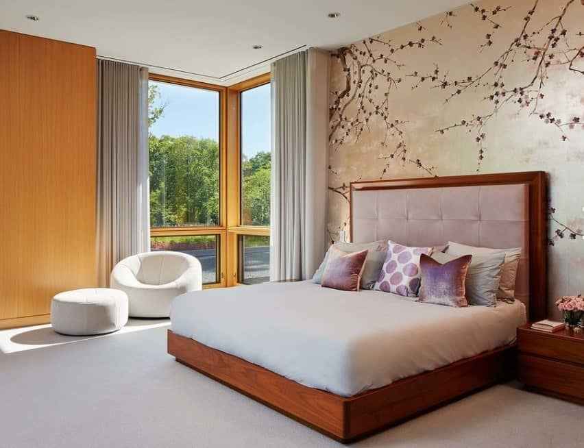 This Asian primary bedroom looks sophisticated with a cherry blossom themed accent wall and polished wood furnishings. A modern club chair and ottoman looks inviting as it sits near the corner window with views of the natural outdoors.