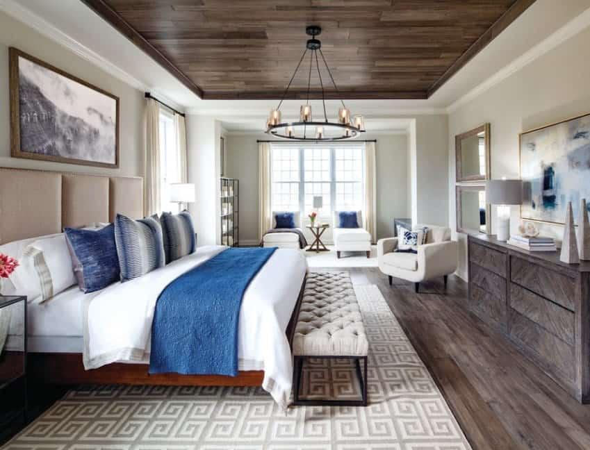 Blue pillows on a white bed or chairs easily achieve a coastal look for this room. The pallet tray ceiling with candelabra chandelier pairs up with the wooden dresser and wood flooring for visual warmth while the tufted bench and patterned rug inject visual texture to the overall look.