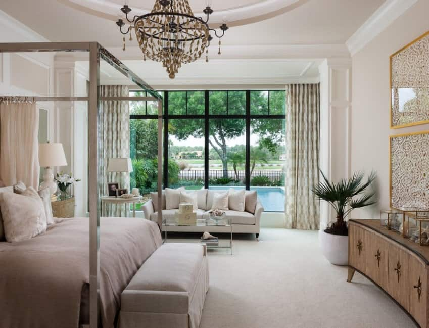 This luxurious master bedroom is furnished with a decorative tray ceiling with chandelier, a four-poster bed, elegant crown moldings, carpet flooring, and a cozy sitting area. The view behind the sofa, however, looks even more fantastic as the floor-to-ceiling draperies open up to reveal large windows that display the patio embellished with trees, plants, and a pool.