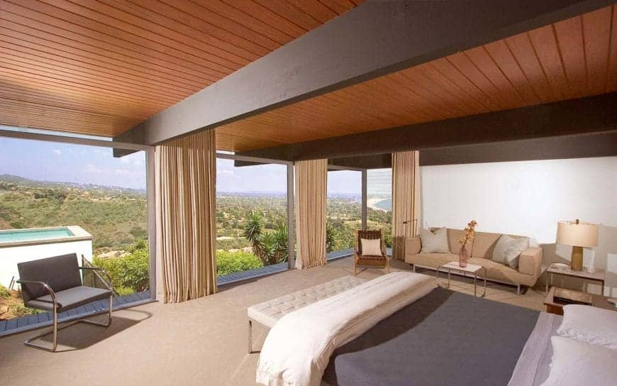 Everything in this room fades into the background when the curtains are opened up to reveal the stunning outdoor views. The midcentury-style chairs and sofa look stylish without obstructing the room's centerpiece.
