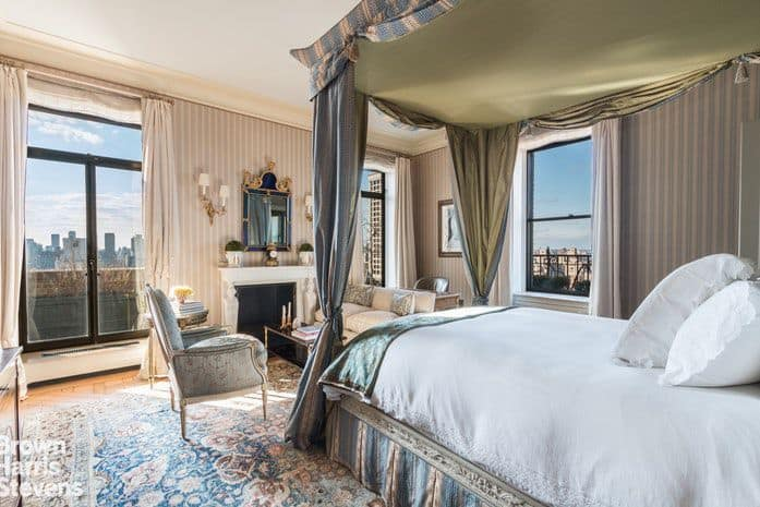 Matching draperies and vertical-patterned interior wallpaper fashioned with neutral tones set the stage for a timeless look as well as a comfy and cozy primary bedroom emphasized with a four-poster canopy bed facing the sitting area by the fireplace. On the other hand, the large windows with black frames displaying an impressive view of the city skyline and skyscrapers offset with a modern appeal.