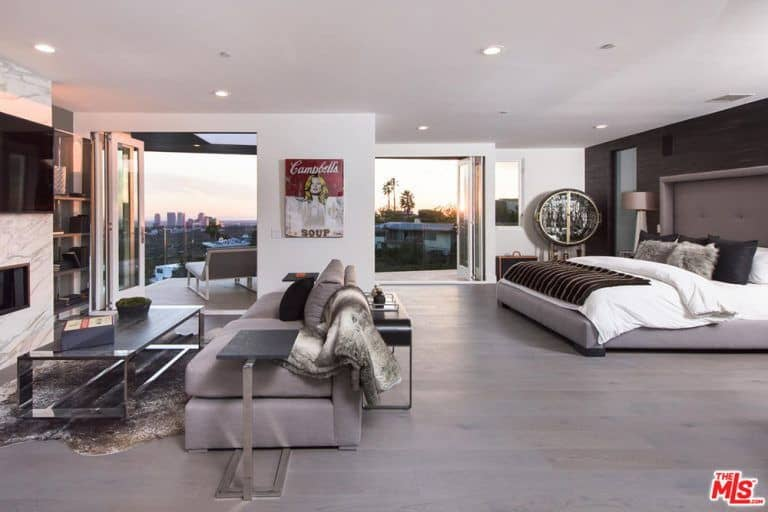 A spacious modern primary bedroom fills the space with warm tones coming from the matching gray primary bed, sofa, and wood flooring. A sitting area facing an electric fireplace below the wall-mounted TV offers some entertainment away from the bed while the glass folding doors leading to the balcony open up to a sweeping view of the outdoors.