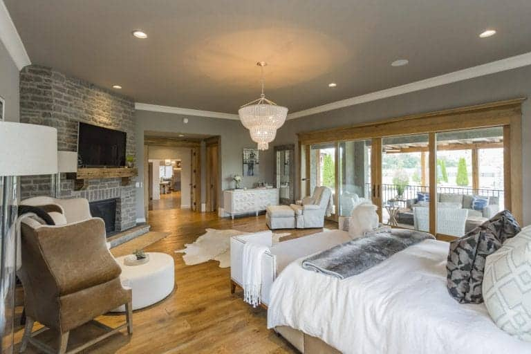 A crystal chandelier serves as a glamorous centerpiece while the different types of seating are drawn towards the stone fireplace at the left corner of the room with a wall-mounted TV. Comfortable throws and pillows and ottomans make the recliner seat, modern chaise lounge, and wingback chair all create inviting sitting areas in the rustic modern primary bedroom.