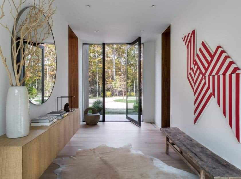 Mid-century foyer featuring white walls with wall decors and ceiling. The hardwood flooring looks perfect with the foyer's style.