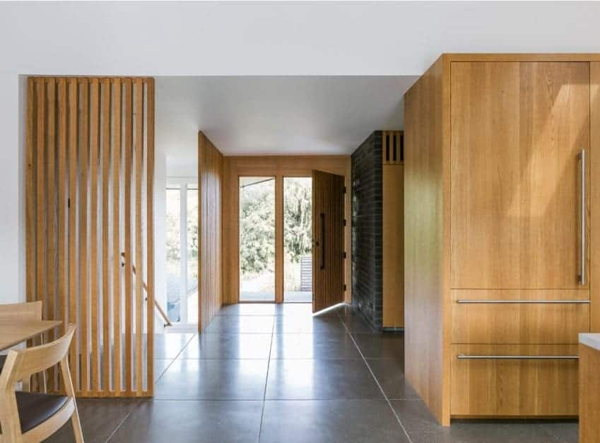 Mid-century foyer with tiles flooring and white walls, along with walnut finished other home details.