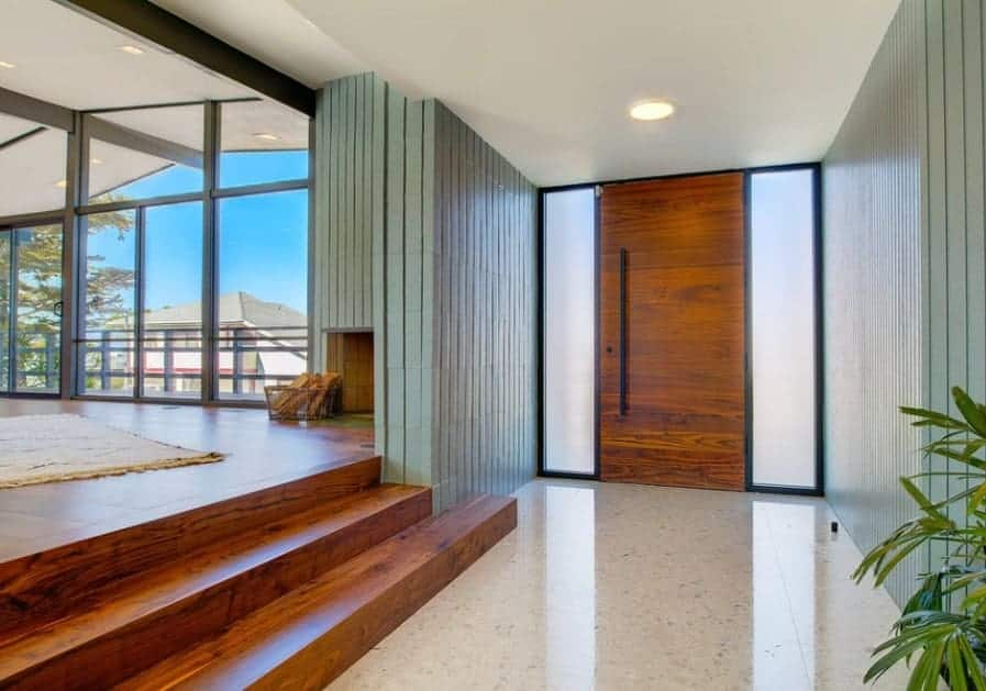 Mid-century foyer featuring tiles flooring leading to the living room set on the hardwood floors.