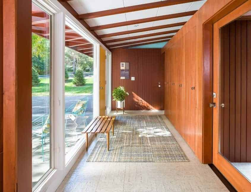 Mid-century foyer with brown wooden walls and tiles flooring topped by a rug. The glass windows let the sunlight through and overlook the beautiful outdoors.