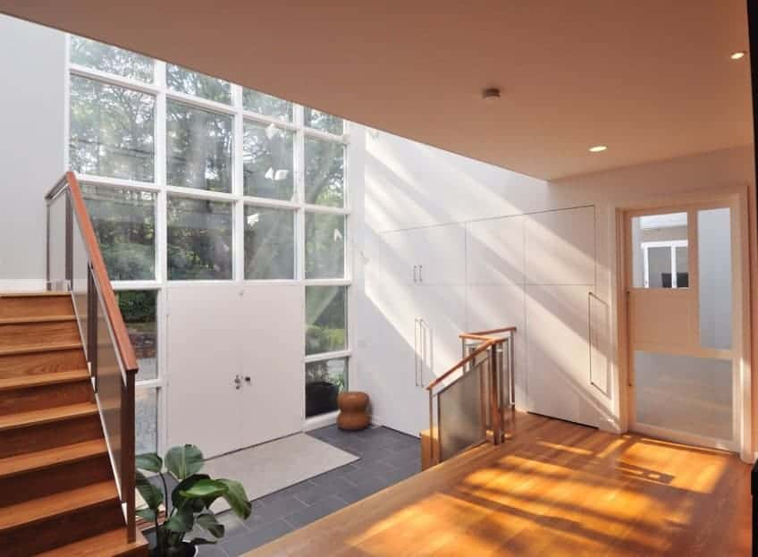 Mid-century foyer with multiple glass windows letting sunlight through and overlooks the beautiful outdoor area outside.