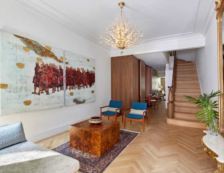 Mid-century foyer featuring a white walls with a stunning wall decors. The space is being lighted by a grand chandelier.