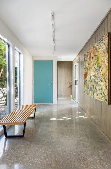 Mid-century foyer featuring a smooth tiles flooring, white and wooden walls, floor to ceiling glass windows and a set of track lighting.