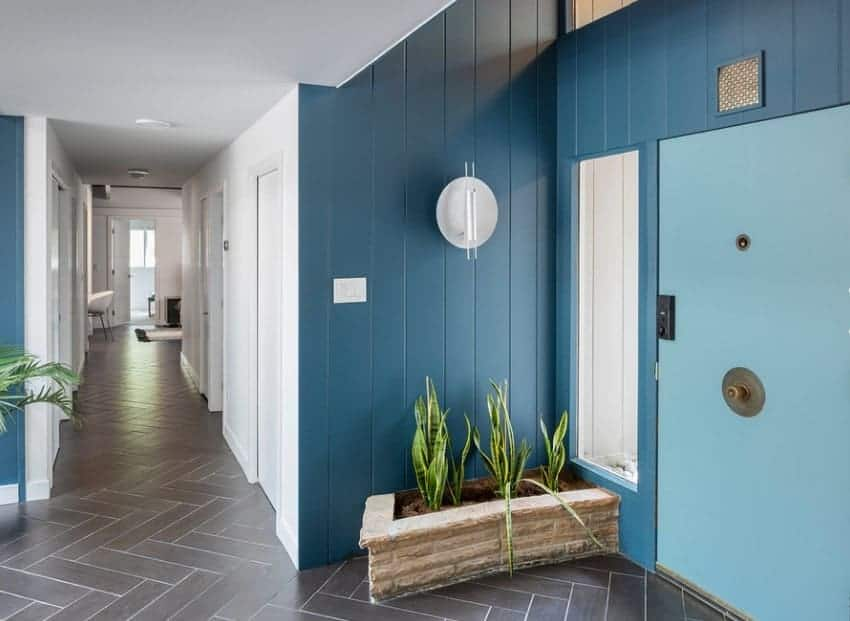 Mid-century foyer with tiles flooring, white walls mixed with blue shade and plants on the corners for additional colors.