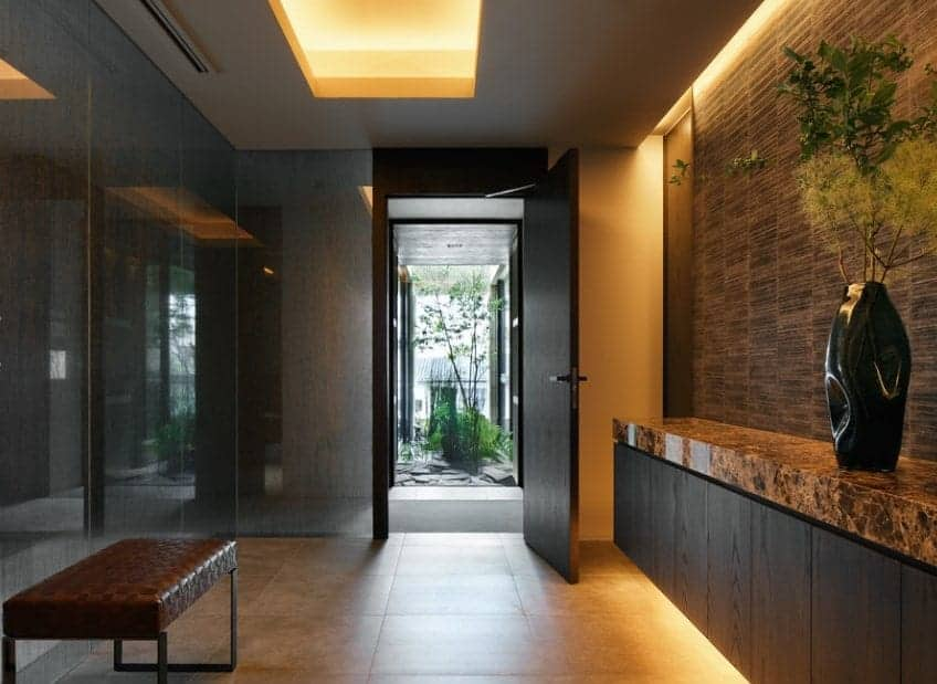 Elegant mid-century foyer featuring a tiles flooring, stylish walls and warm white ceiling lights for a gloomy vibe.