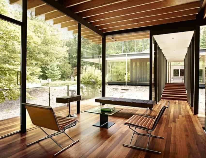 Mid-century foyer with a modern touch. The hardwood flooring blends well with the floor to ceiling glass doors and windows overlooking the outdoor area.