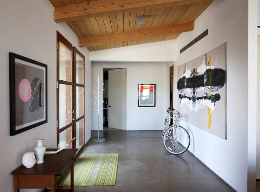 Mid-century foyer with white walls and artistic wall decors. The wooden ceiling looks great with the foyer's style.