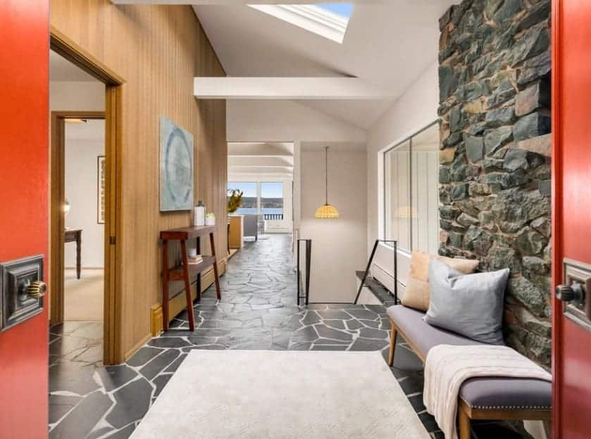 Mid-century foyer featuring a very stylish flooring topped by a rug. The white, wooden and stone walls look perfect with each other.