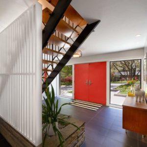 Midcentury foyer design with red door
