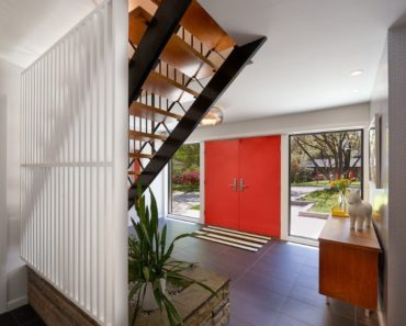 Midcentury foyer design with red door
