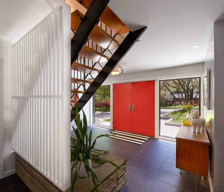 Mid-century foyer with tiles flooring, smooth white walls and red main door. The clear mirror windows on both side lets sunlight through, overlooking the outdoors as well.