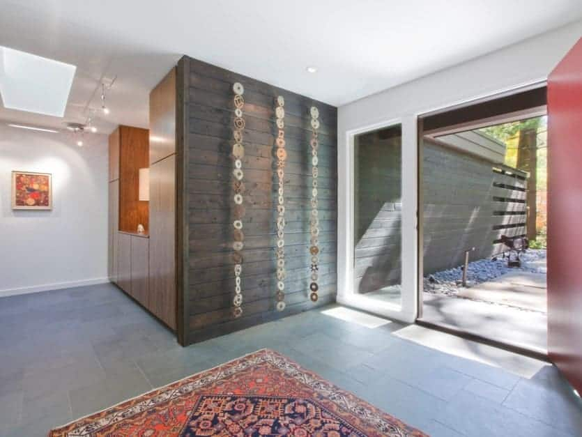 Mid-century foyer featuring white walls, tiles flooring topped by a rug and a set of track ceiling lights.