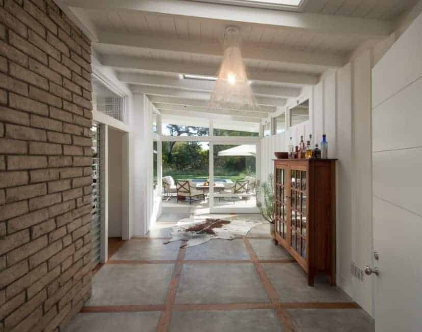 Mid-century foyer with white walls and ceiling with beams. Skylights brighten the space.