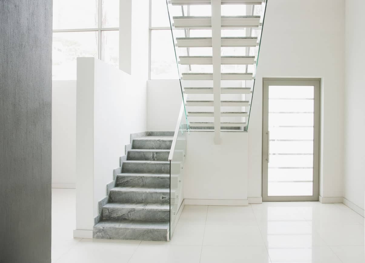 This foyer is surrounded by smooth white flooring, walls and ceiling. The staircase's steps are very stylish and it feature glass railings.