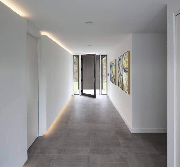 This entry is surrounded by white walls and alluring wall displays. The flooring also looks good with the home's style.