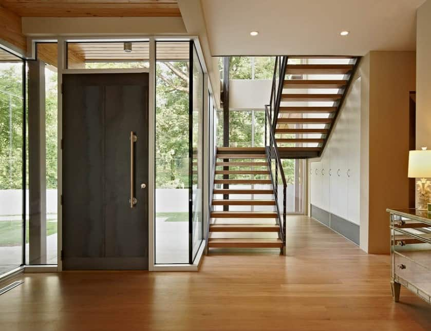 This foyer offers a half-turn staircase with beautiful steps. The flooring looks perfect with the glass walls and windows as well.