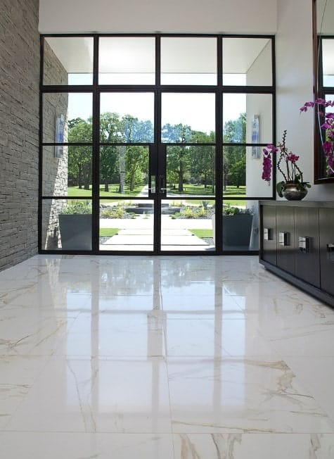This entry boast marble tiles flooring and brick wall along with high glass door. The style of this entry is very modish.