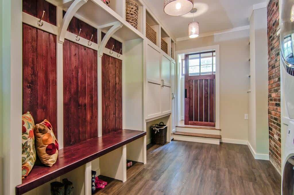This is a super fancy mudroom with vinyl flooring, a brick wall, and a lot of different storage compartments. It carries more of a modern touch to it than an ordinary mudroom.