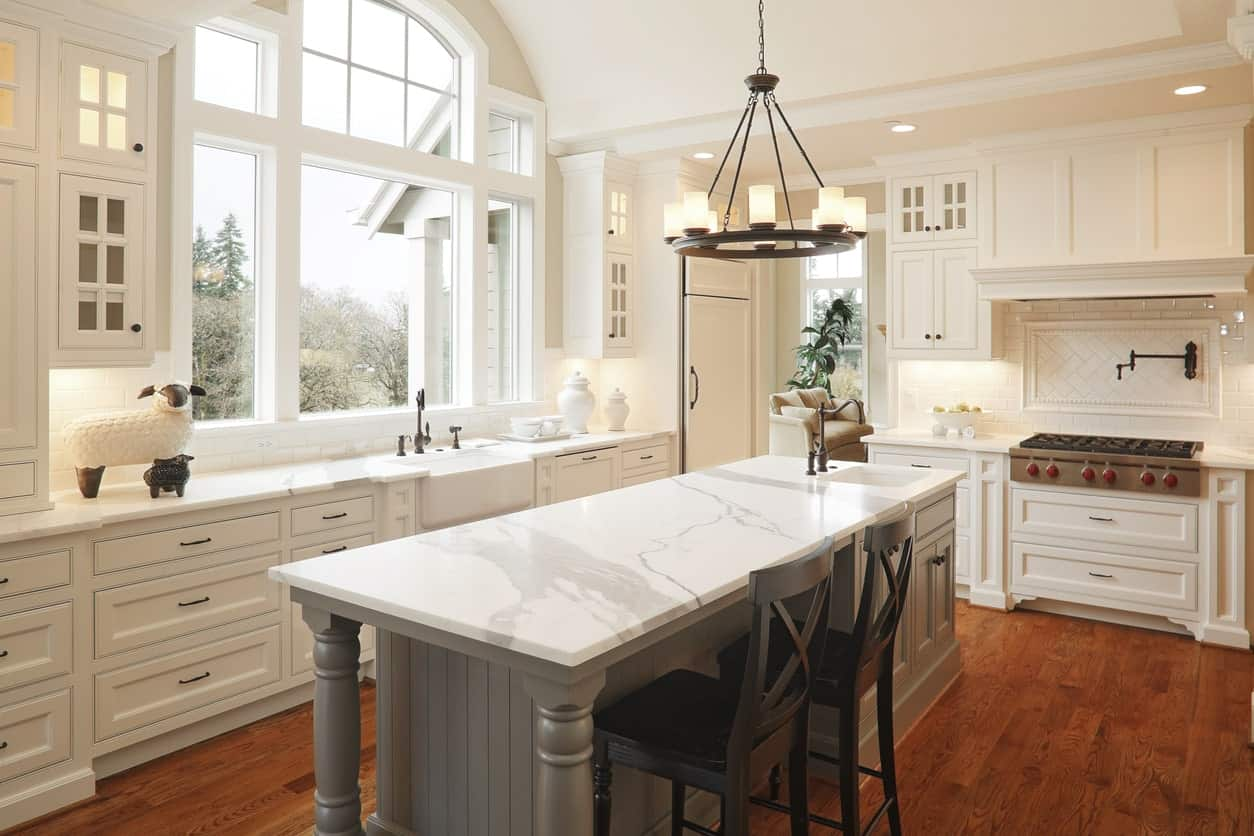 This kitchen features an all-white details except for the flooring and the narrow center island. The smooth marble counters are so stunning.