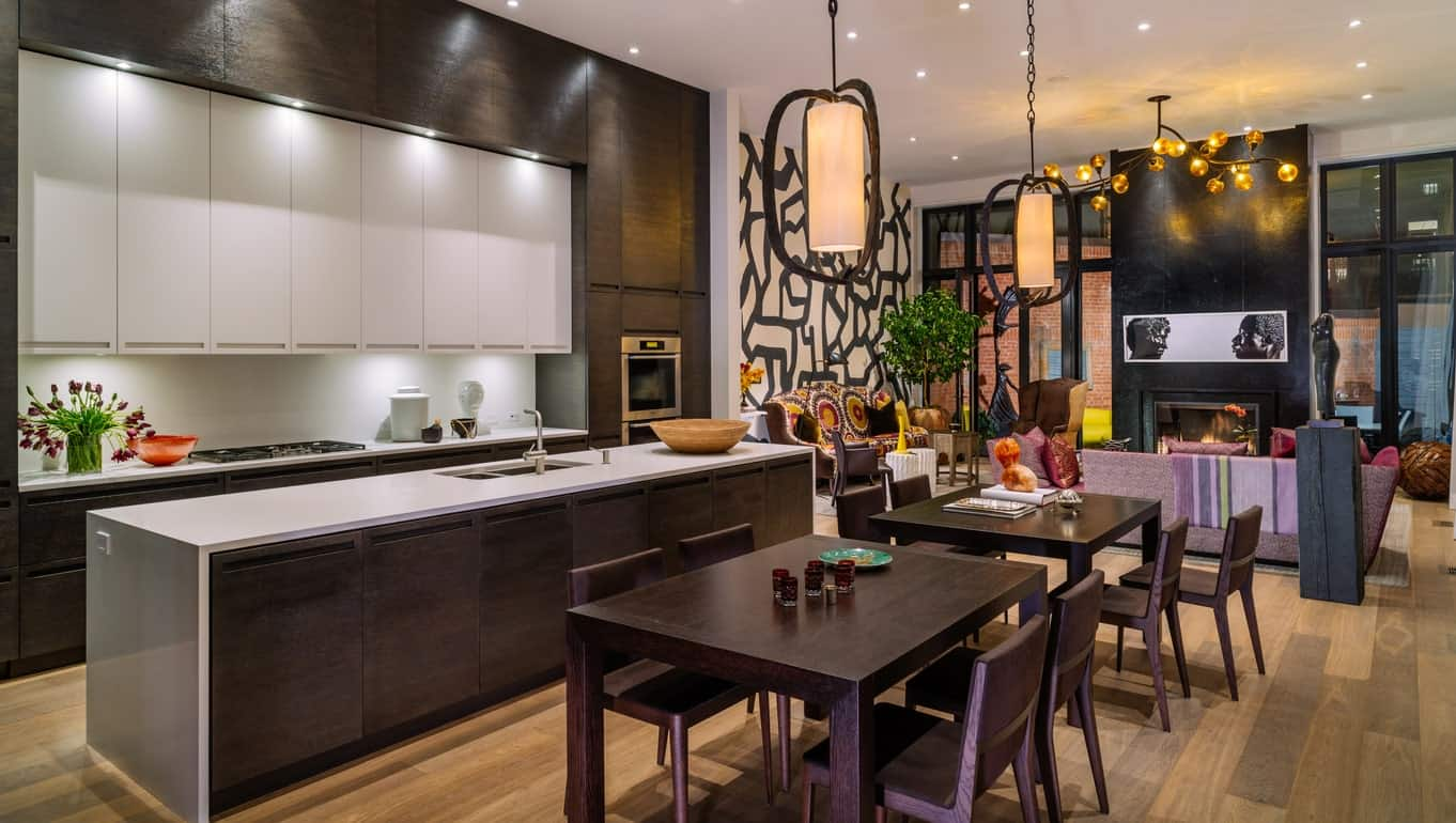 This stylish kitchen features dark hardwood shade and warm lights. The kitchen also offers a narrow center island with a smooth white countertop.