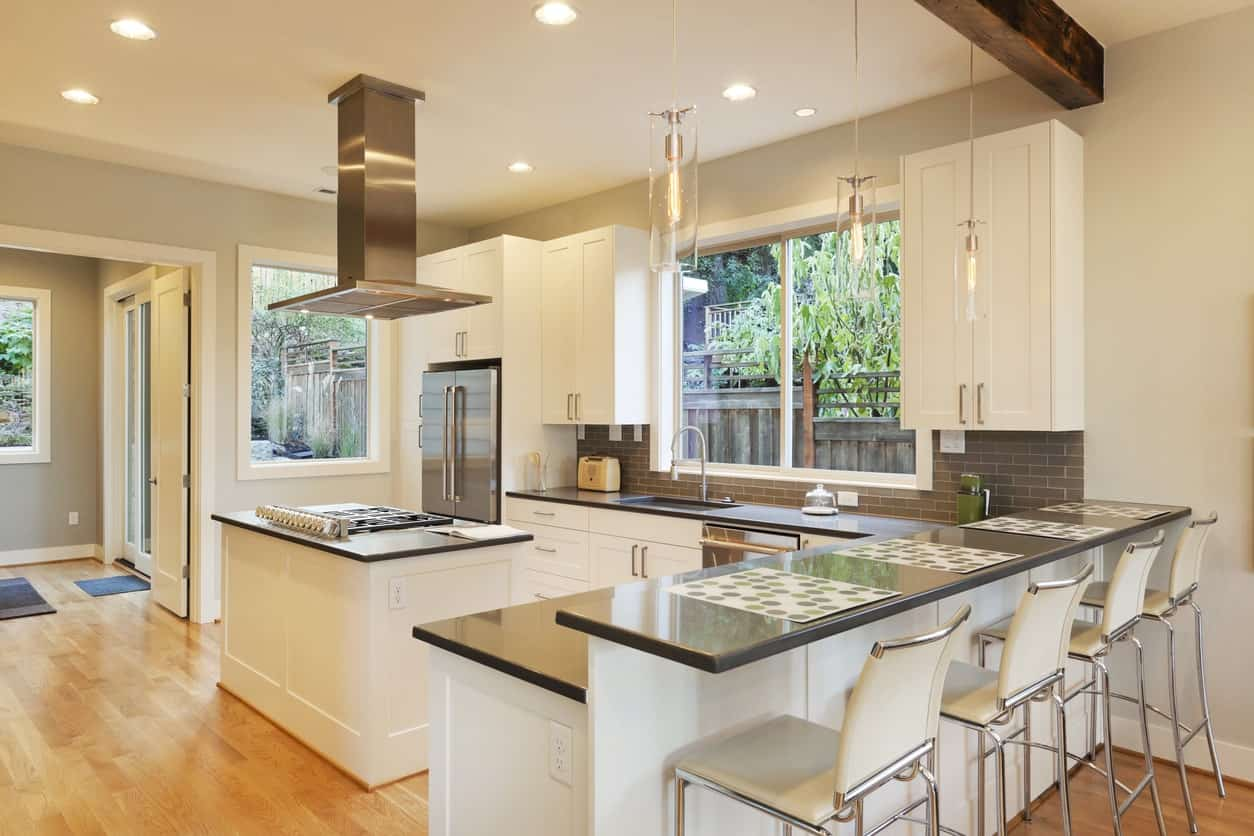 This kitchen with white cabinetry and glamorous pendant lights are just perfect and has a dark granite counters. There's a narrow center island for additional meal preparation space.