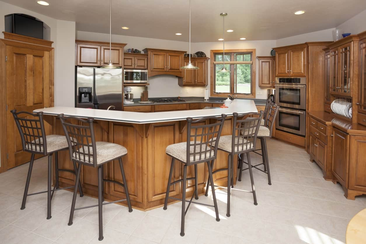 This kitchen features walnut finished details and white walls and flooring. The narrow center island offers enough space for a breakfast bar.