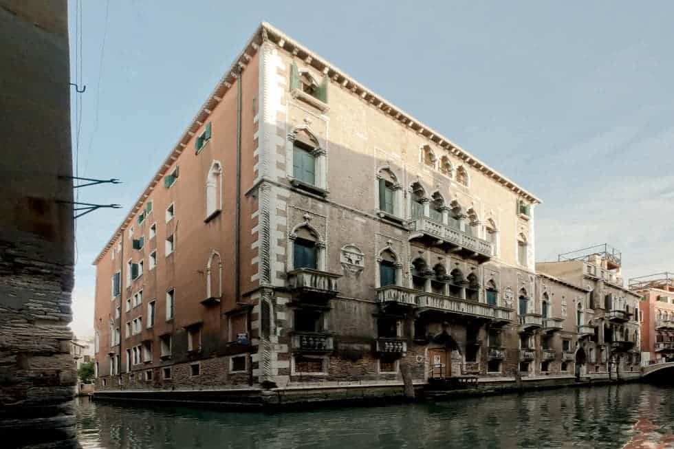 This is an exterior view of the apartment building showcasing the canal and the boat dock that leads to the main entrance. Image courtesy of Toptenrealestatedeals.com.